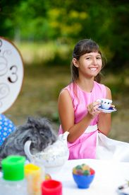 stock photo of alice wonderland  - Girl sits at table and holding a cup of tea - JPG