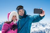 Happy couple taking selfie by smartphone over winter background. Man taking selfie with cheerful gir poster