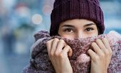 Winter portrait of young beautiful woman covering face with woolen scarf. Closeup of happy girl feel poster