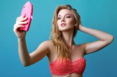 Beautiful Young Blonde Woman Posing In Studio In Swimsuit And With Phone poster