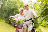 old age, people and lifestyle concept - happy senior couple with bicycles at summer city park poster