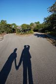 Shadows Of Two People Holding Hands On Road