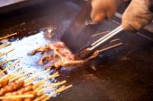 Roasting squid shashlik in a Chinese open market