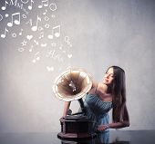 Beautiful woman using an old gramophone with notes coming out from it
