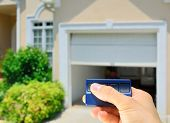 stock photo of garage  - Garage Door Opener opening a residential garage door - JPG