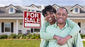 Happy African American Couple In Front of Beautiful House and For Sale Real Estate Sign. poster