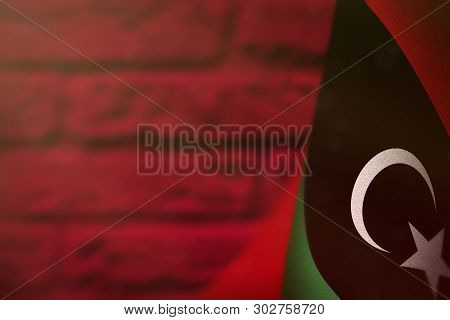 poster of Libya Hanging Flag For Honour Of Veterans Day Or Memorial Day On Red Blurred Painted Brick Wall Back