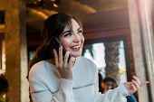 Happy Young Woman Talking On Cell Phone While Sitting Alone In Coffee Shop. Smiling Girl Has Telepho poster