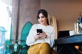 Young Woman Reads Text Message On Phone While Sitting Coffee Shop. Girl Chatting With Friends On Cel poster