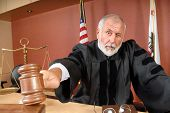 stock photo of courtroom  - Older distinguished judge making his ruling in the courtroom - JPG