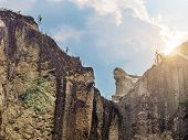 Hard Rock Cliff And Blue Cloudy Sky With Sun Light Flaring From Behind The Cliff poster