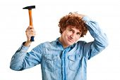 Clumsy man with headache after hitting himself with a hammer isolated on white