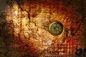 stock photo of treasure map  - Old brass compass lying on a very old map - JPG