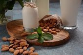 Almond Milk In Glass Bottles With Almonds On Background. Vegan Diary Concept. Healthy Food And Drink poster