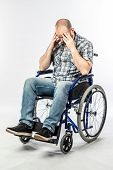 Disabled man in a desperate and sad wheelchair with his head in his hands. Concept of difficulty and poster