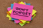 do not forget reminder - a stack of colorful sticky notes on cork bulletin board