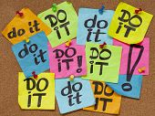 fighting procrastination concept - do it phrase on color sticky notes posted on a cork bulletin boar