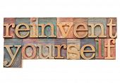 reinvent yourself - personal development concept - isolated text in vintage wood letterpress printin