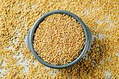 high angle view of a gray ceramic bowl with of tender wheat kernels on a table full of some more ten poster