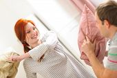 picture of pillow-fight  - Happy young couple having pillow fight in room - JPG