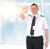 Cheerful airline pilot wearing uniform with epaulettes sending greets with hand, standing at the airports big window