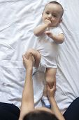 Baby Massage. Mom Doing Gymnastics With Kid. Mommy Massaging Cute Baby Boy. Moving Babys Legs To He poster