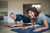 A Senior Couple Indoors At Home, Doing Exercise On The Floor. poster