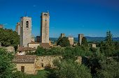 View Of Rooftops And Towers With Trees And Blue Sunny Sky At San Gimignano. An Amazing Medieval Town poster