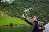 Tourist Feeding Bread To Seagulls. Young Man Feeding Seagulls Flying Over The Ferry Boat. Man Travel poster