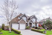 Beautiful exterior of newly built luxury home. Yard with green grass and stone. poster