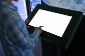 Woman Hand Using White Blank Interactive Touchscreen Display Of Electronic Multimedia Kiosk In Dark  poster