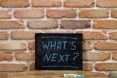 Chalk board with the phrase WHATS NEXT? drown by hand and chalks on wooden table on brick wall back poster