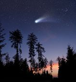 stock photo of starry night  - A bright comet is flying in the starry evening sky - JPG