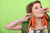 a female cook wearing carrots as earrings