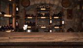 Defocused Dark Wine Cellar Background With Wooden Table In Front poster