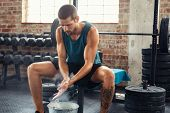 Fitness young man rubbing hands with chalk magnesium powder. Determined muscular guy preparing for w poster