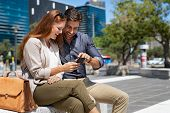 Happy young couple using smartphone together outdoor in a modern square. Smiling mature couple using poster
