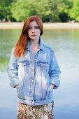 Young Woman Wearing Denim Jacket Over Summer Dress Standing By Lake - Authentic Real People poster