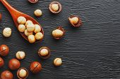 Shelled Macadamia Nut And Peeled Macadamia Nut On A Black Textural Background In A Wooden Spoon. Low poster