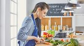 A Young Woman Prepares Food In The Kitchen. Healthy Food - Vegetable Salad. Diet. The Concept Of Die poster