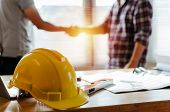 Yellow Safety Helmet On Workplace Desk With Construction Worker Team Hands Shaking Greeting Start Up poster