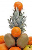 closeup of a pile of fruits like pineapple, kiwis and oranges