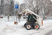 image of bobcat  - small excavator bobcat working on the street cleaning snow - JPG