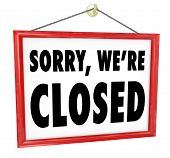 Sorry We're Closed sign hanging in a store window to represent closure, bankruptcy, after hours or g