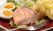 Grilled salmon served on slivers of fried cougette with a hard-boiled egg,  salad and mashed potato
