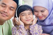 Southeast Asian family listen mp3, sharing headphone. Muslim family living lifestyle