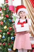 Little girl with Christmas toys in festively decorated room