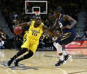 BROOKLYN-DEC 15: Michigan Wolverines guard Tim Hardaway Jr. (10) dribbles the ball past West Virgini