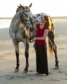 woman with her appaloosa horse on the beach.
