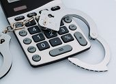calculators and handcuffs on a white background. representative photo of white-collar crime
